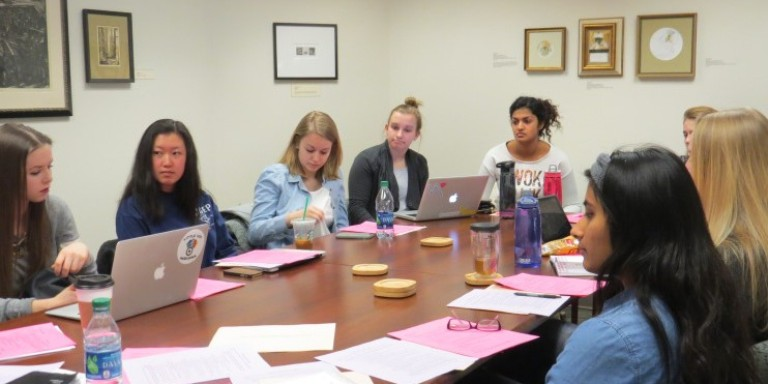 An executive board meeting in progress with students sitting around a large table.